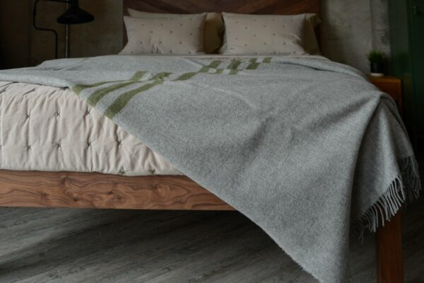 grey marl woollen throw with green stripes shown on a bed