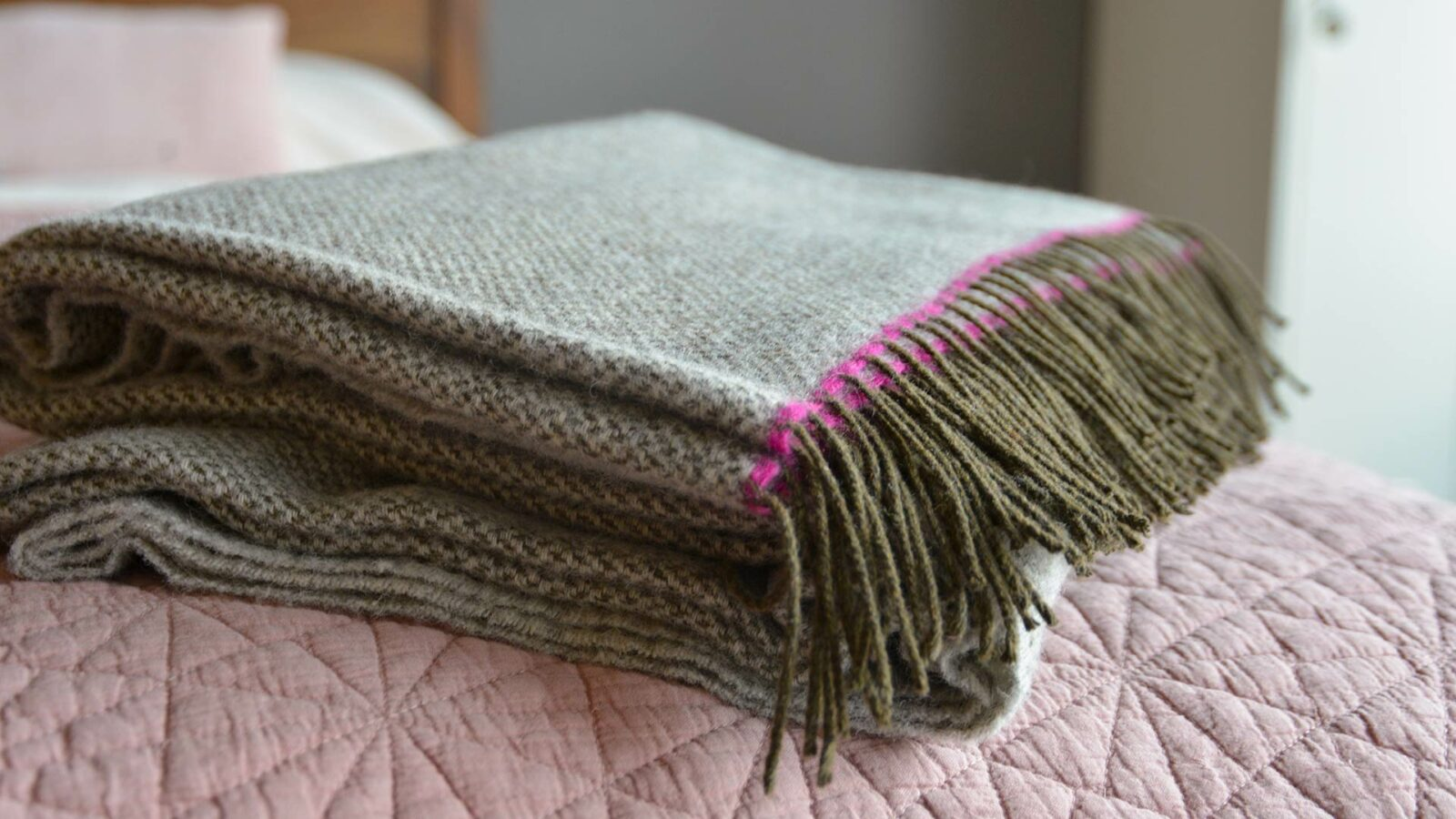 woven pure wool scarf in greys with bright pink contrast edge
