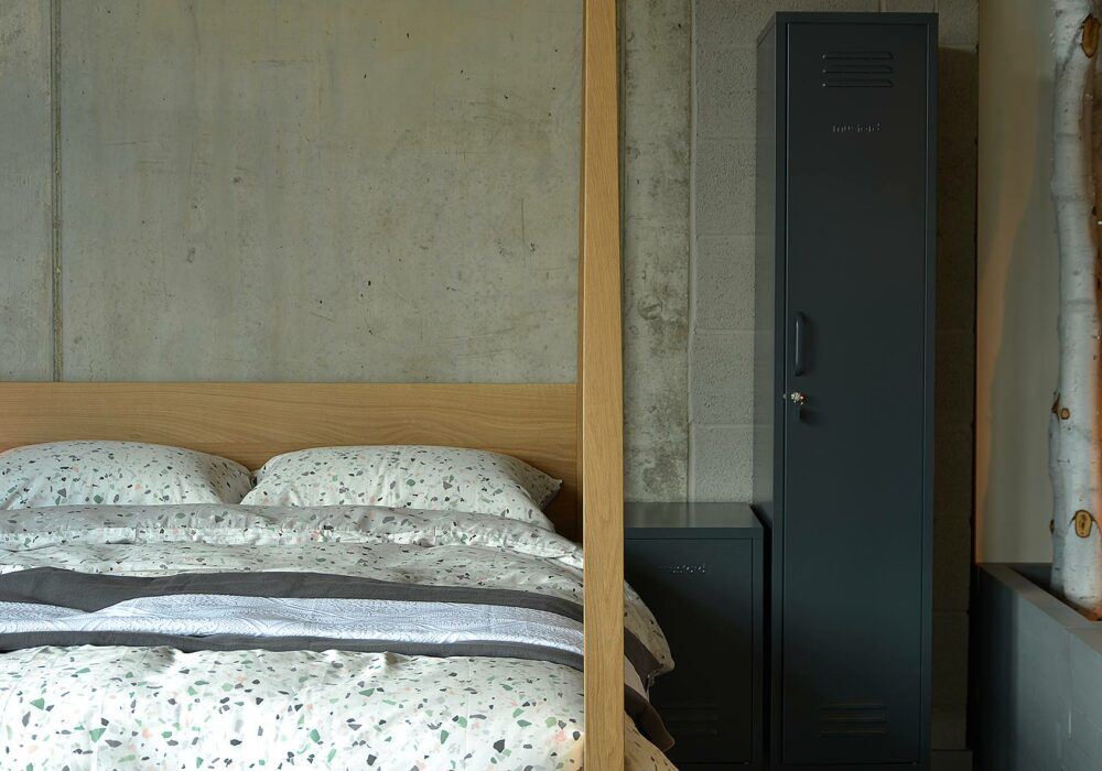 Hatfield Tall Post Bed in Oak shown with Terrazzo print bedding and lockers