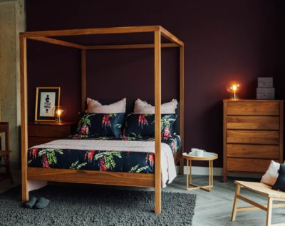 Printed floral bedding on the Walnut Highland wooden 4 poster bed shown with matching walnut drawers