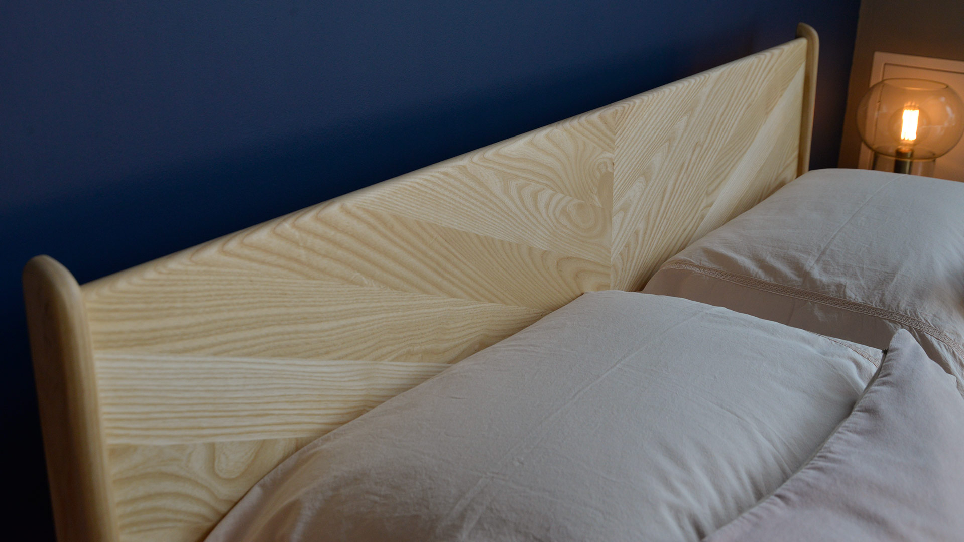 A close view of the chevron pattern Hoxton headboard hand-made from sustainably sourced solid wood.