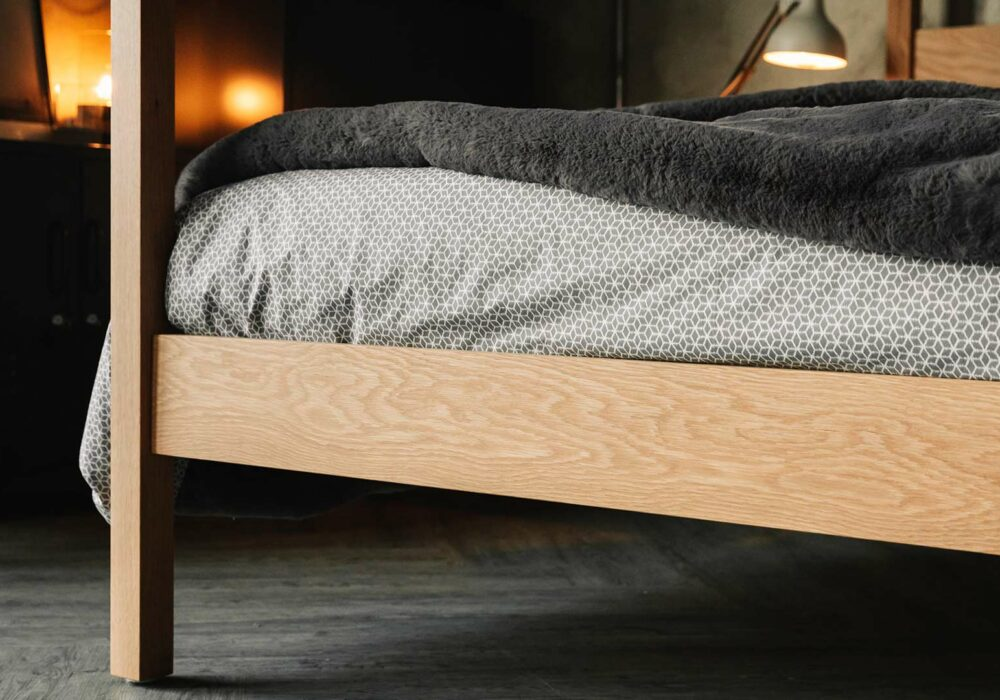 A close up view of the foot board end and post of our Kelham 4 Poster bed in solid wood - oak