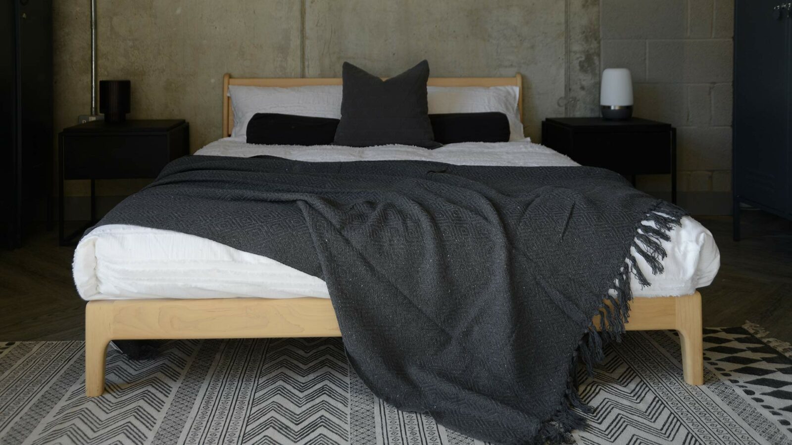 charcoal grey textured cotton rich throw shown on a kingsize wooden bed