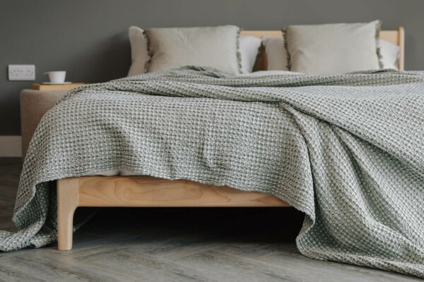 Silver-Green Bedspread displayed on a solid maple bed base