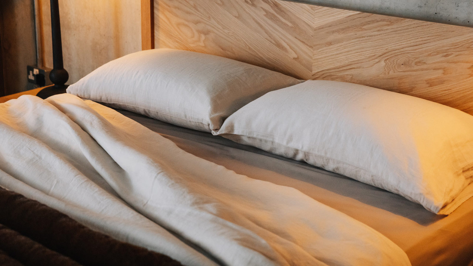 linen bedding on Kelham oak bed showing the hand crafted chevron pattern to the headboard