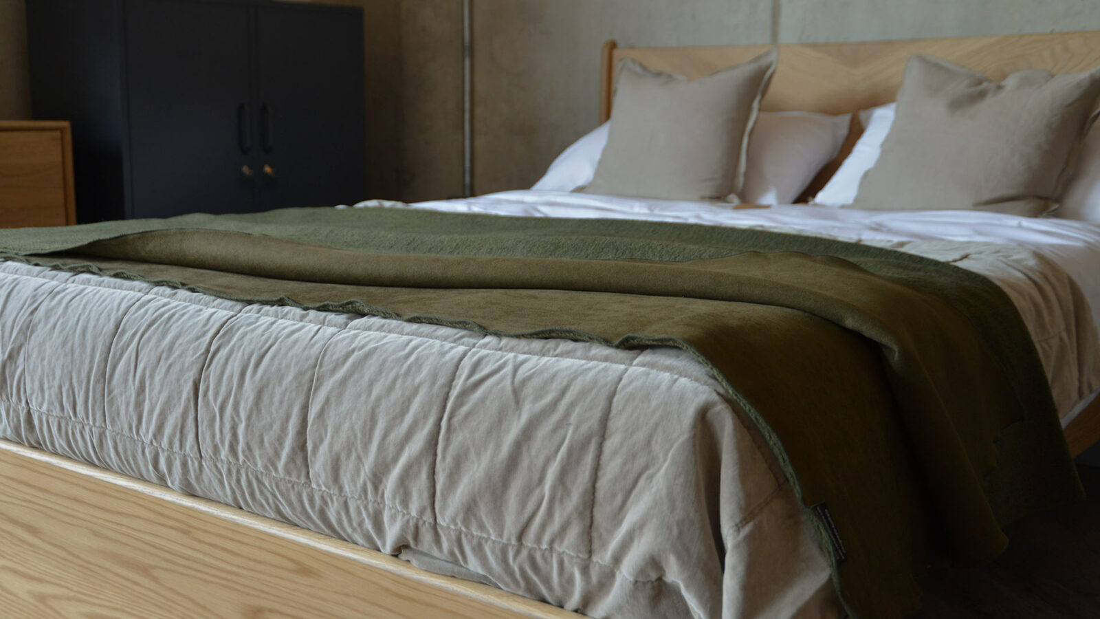 faux sheepskin throw in olive green shown on the end of a bed