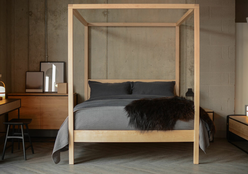 Black accents and blonde woods create a Scandi look for our Orchid 4 Poster bed in Maple