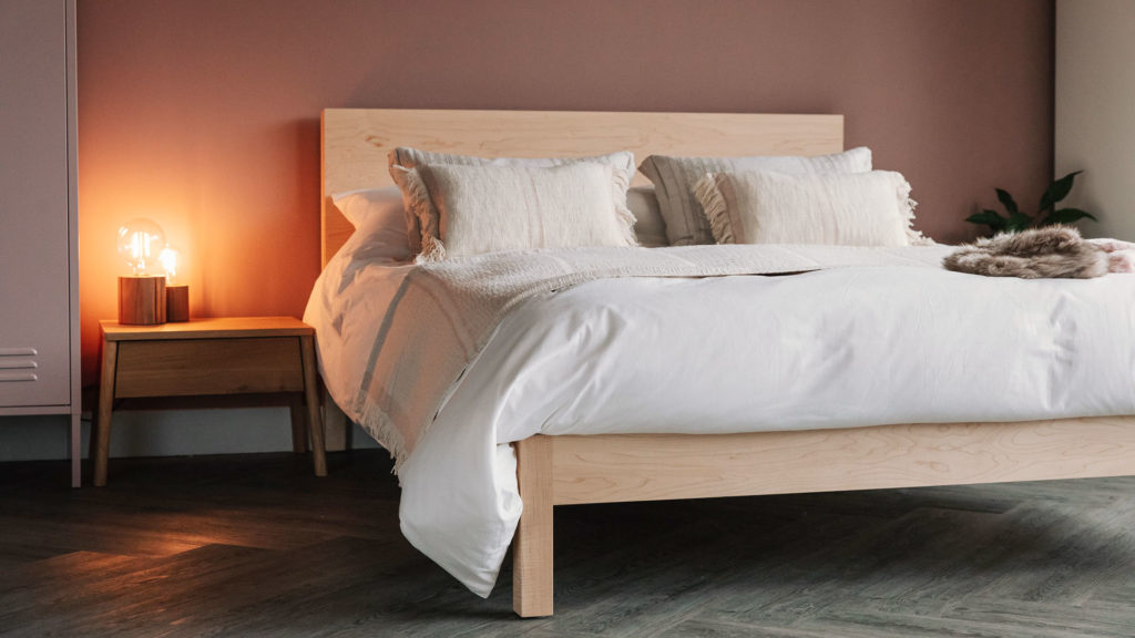 A blush pink bedroom featuring our Maple wooden Malabar bed and Air bedside table