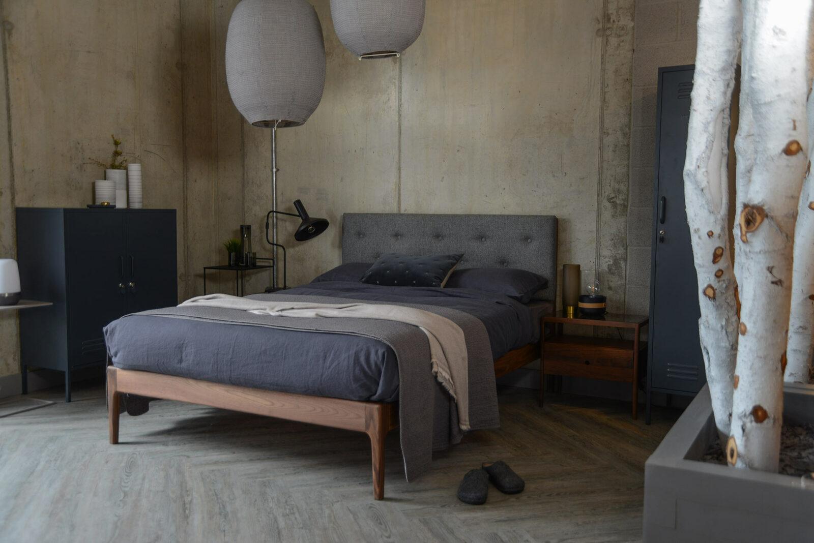 Industrial look bedroom with grey locker storage and grey bedding.