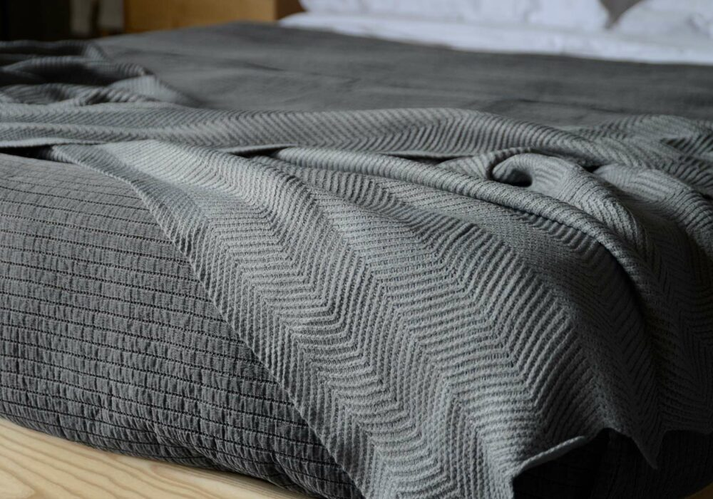 steel grey knitted throw with chevron pattern and scalloped edging