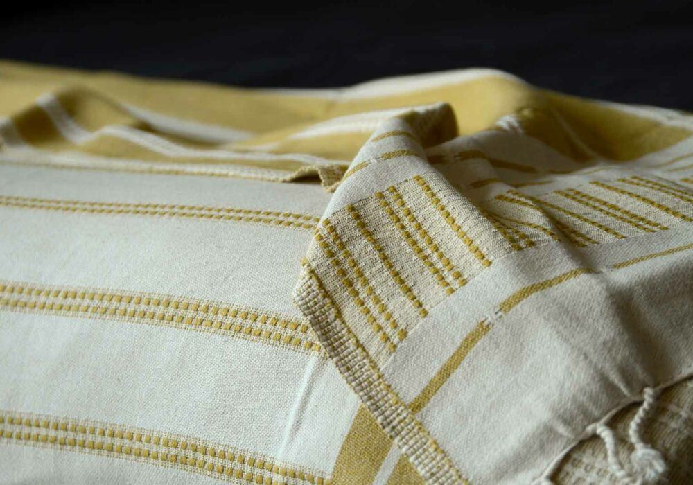 reversible mustard and ivory coloured woven cotton throw