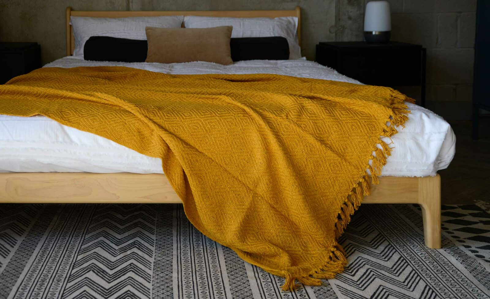 mustard yellow diamond weave throw shown on a kingsize wooden bed