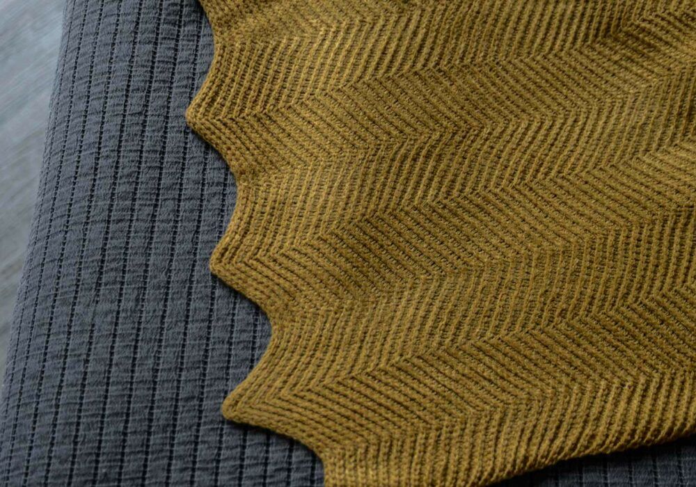 knitted throw in mustard yellow a close up view of the scalloped edge