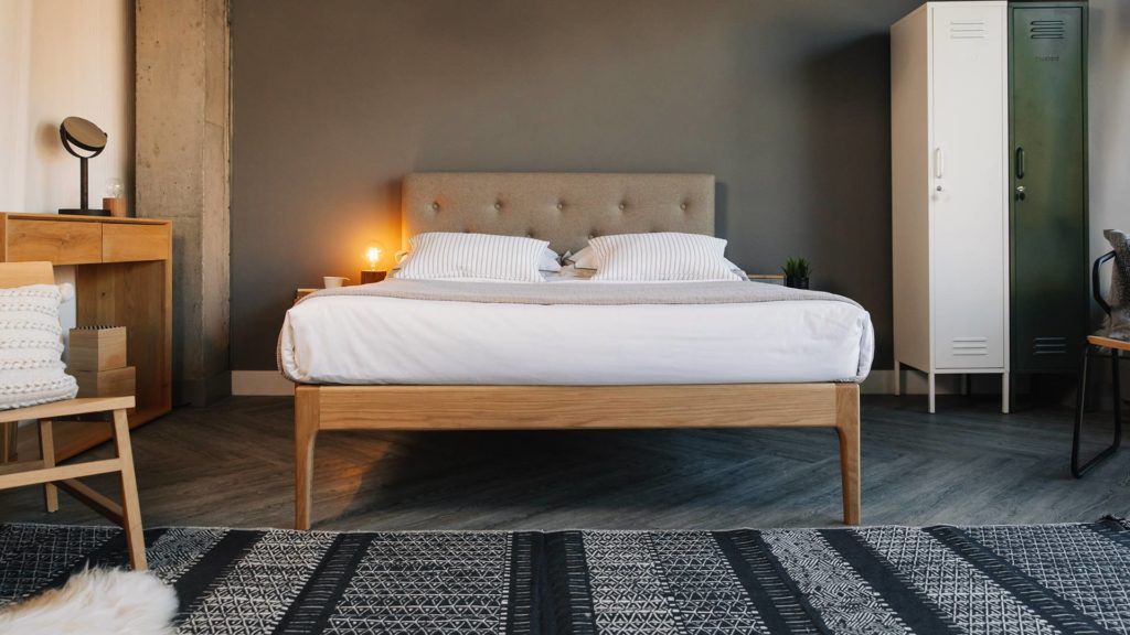 Hand crafted solid wooden bed with upholstered headboard