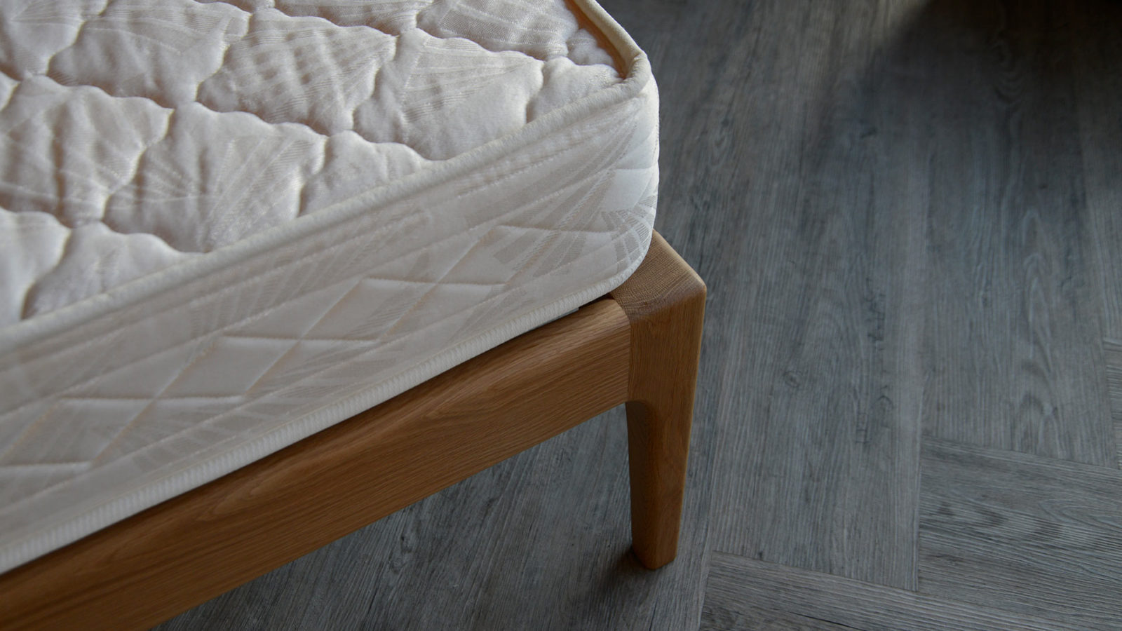 A closer view of the curving solid wood leg of our Camden wooden bed