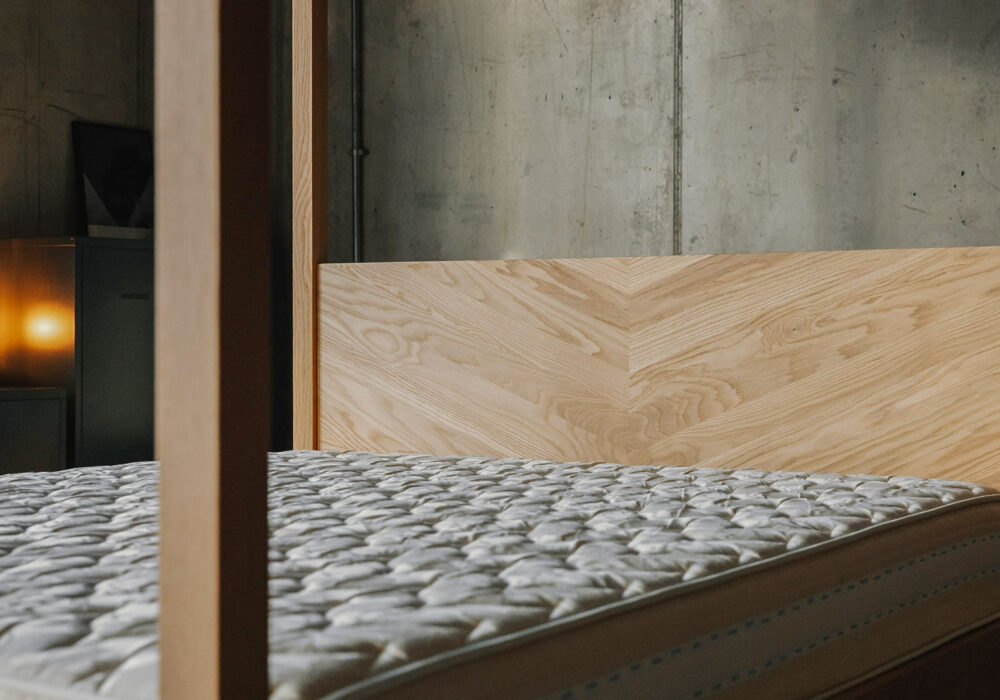 A closer view of the chevron pattern headboard of the Kingsize Kelham 4 Poster bed in solid oak