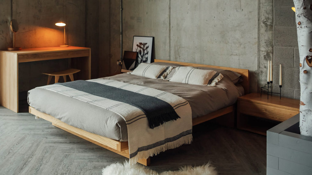 Scandi style bedroom featuring our solid oak Kyoto bed dressed in organic bedding and cotton throws