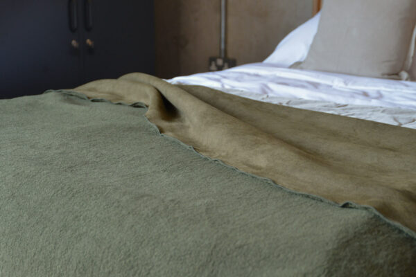 faux sheepskin blanket in olive green shown on the end of a bed