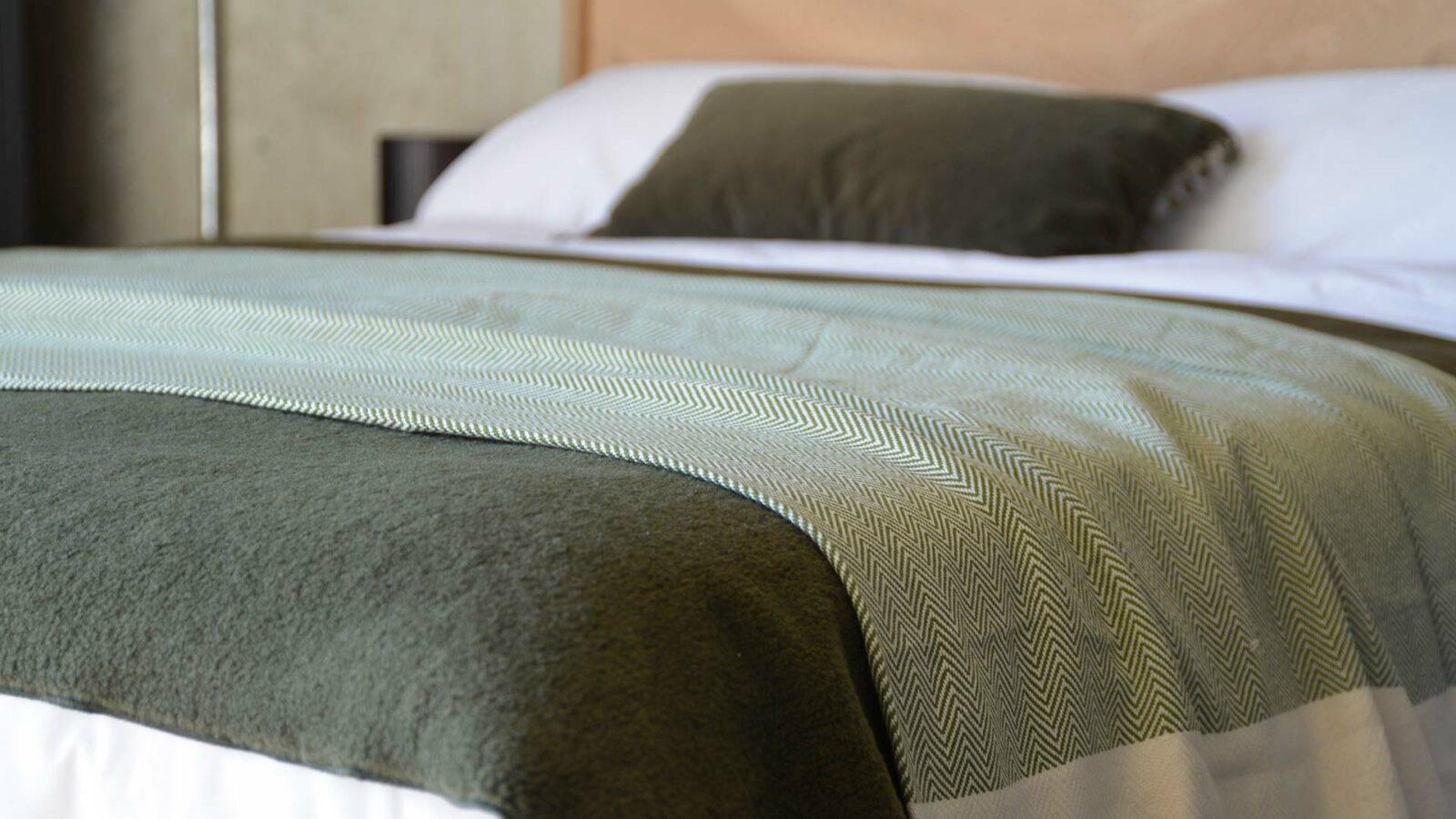OEKO TEX certified woven cotton blanket with herringbone weave in olive green and cream