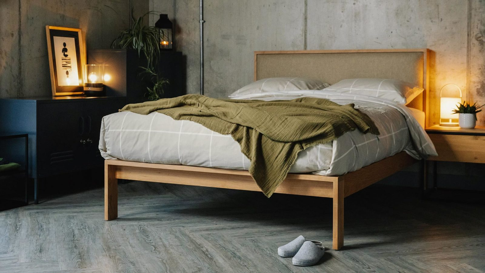 cosy concrete bedroom with wooden Shetland bed with padded headboard