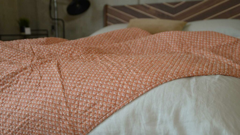 orange quilted throw with a delicate ivory flower pattern