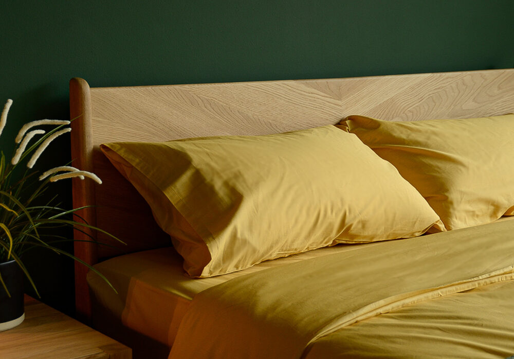 bamboo fibre and cotton duvet set in mustard yellow on a handcrafted oak bed