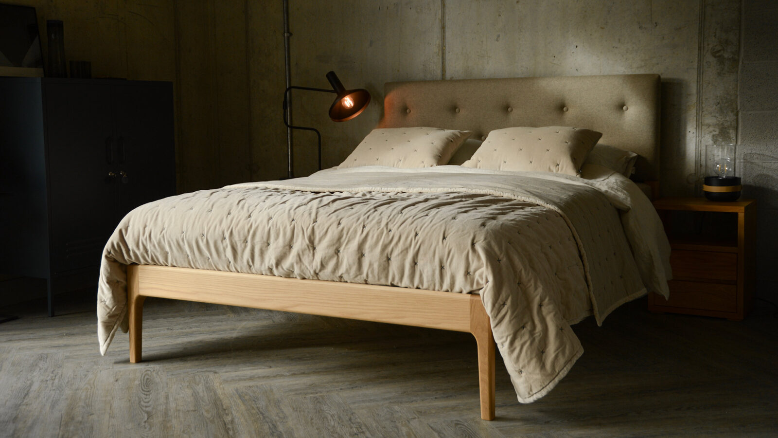 A wool upholstered headboard and oak framed Bloomsbury bed with pale beige velvet quilt and cushions