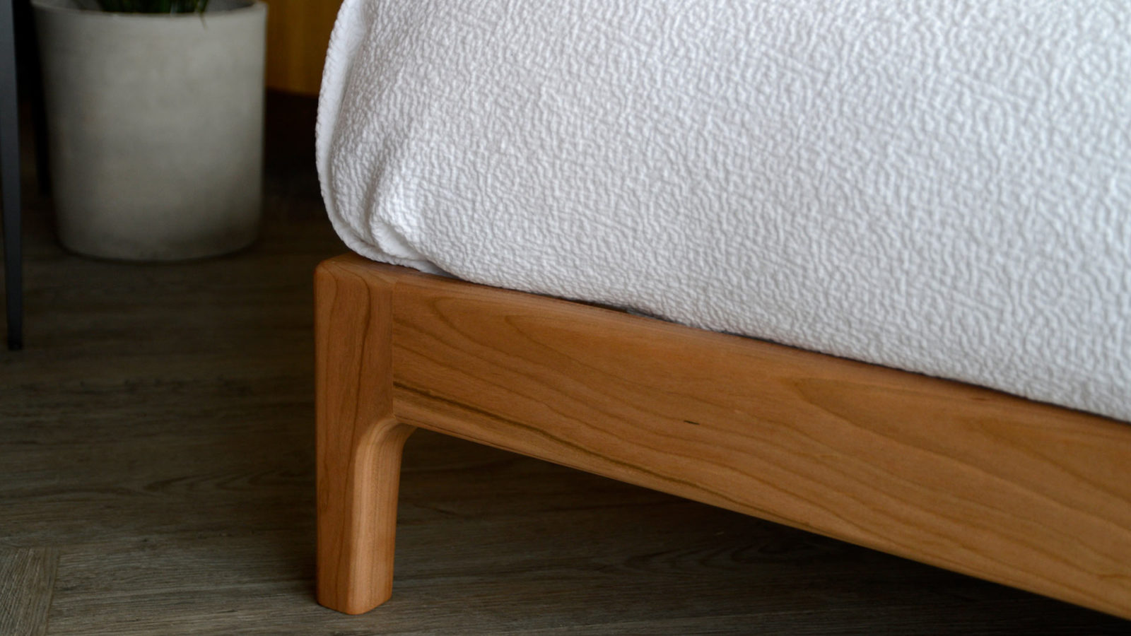 A closer view of the foot of the hand made low Pimlico bed in solid cherry