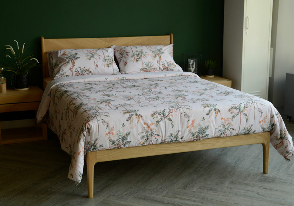 blush pink duvet set with palm tree print shown on an Oak Hoxton bed