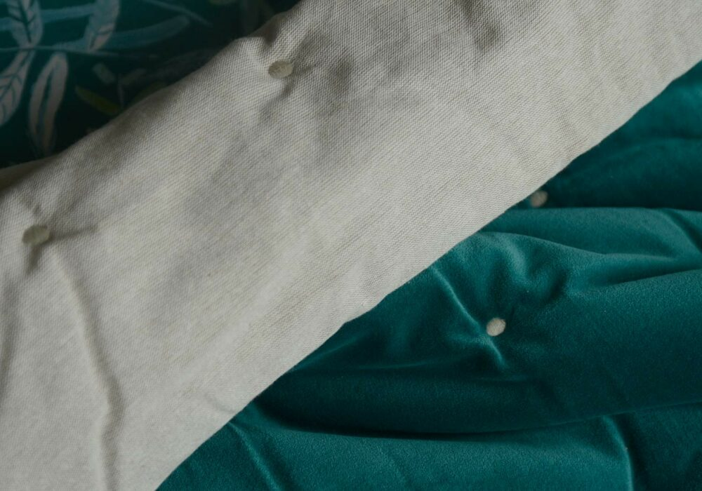 reversible quilted throw in teal coloured velvet and linen like cotton.