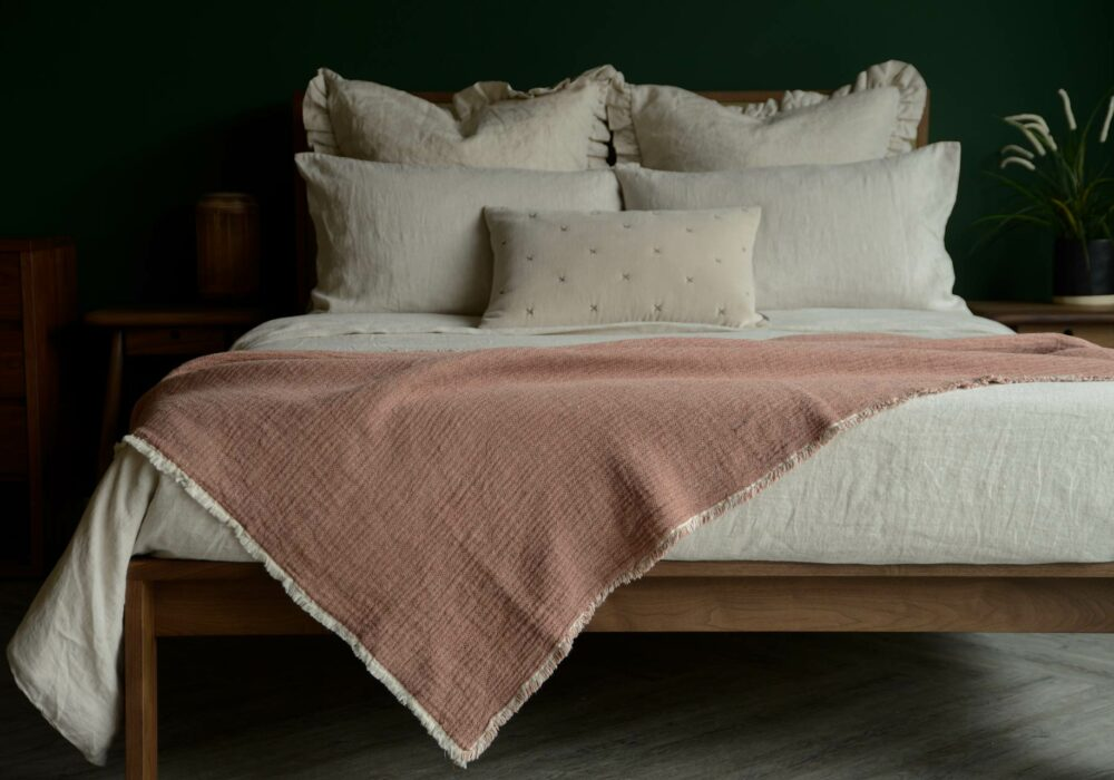 organic cotton reversible throw in blush pink and ivory shown on a kingsize bed