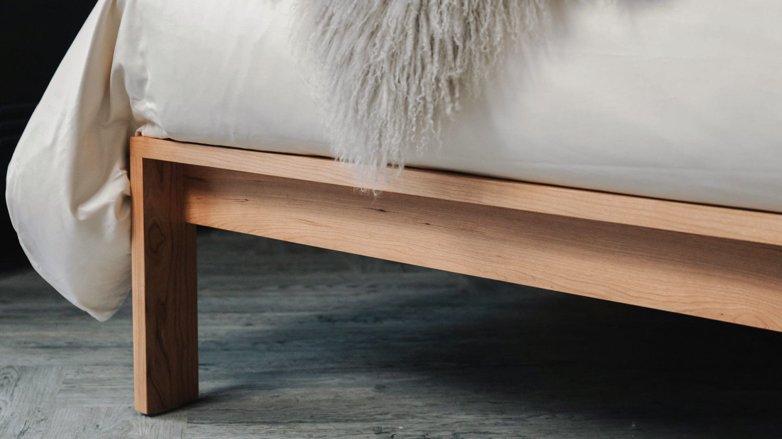A closer view of the leg joint of our Cherry wood Shetland bed and organic cotton sateen bedding