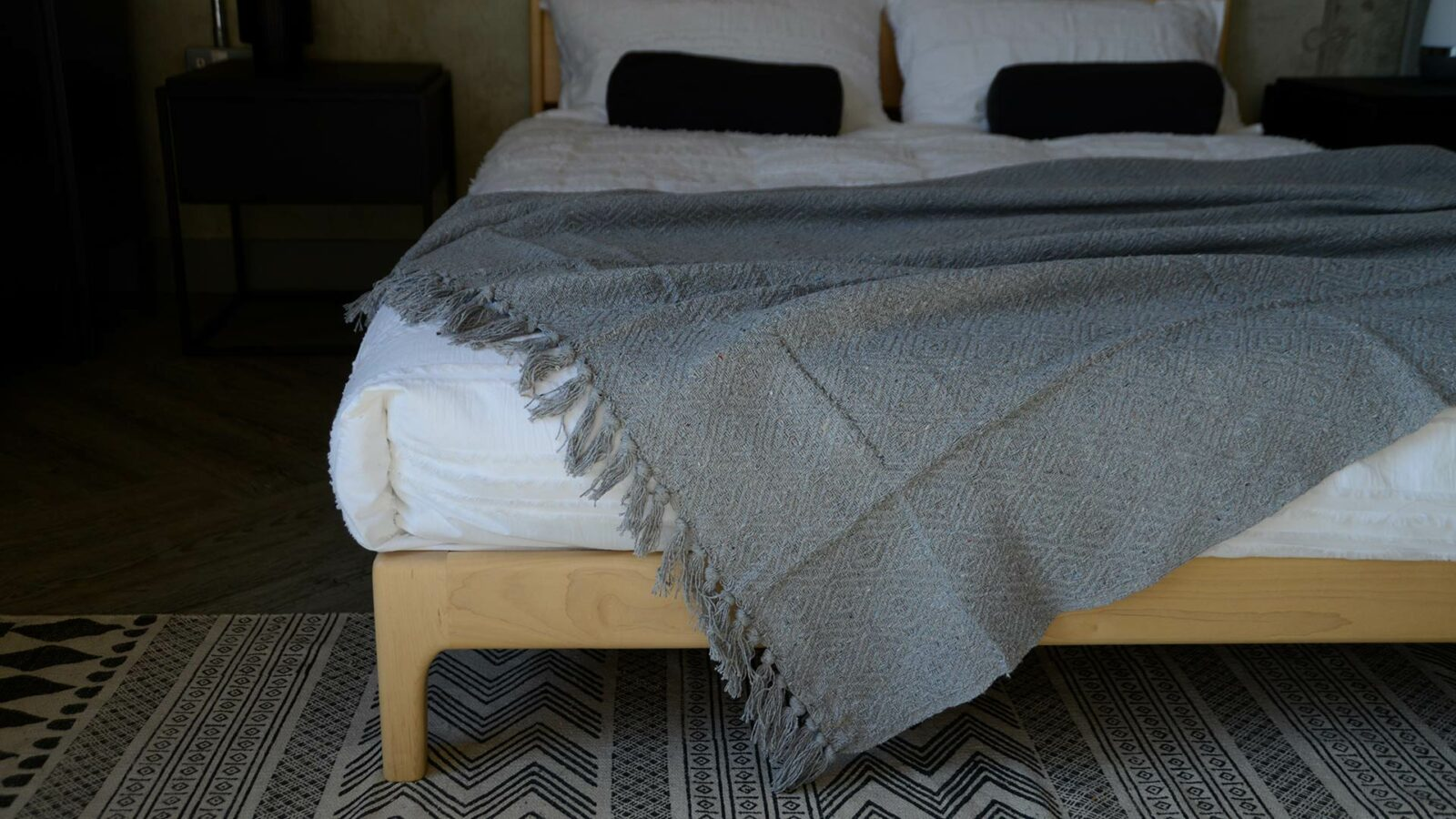 silver grey diamond weave cotton rich throw shown on a kingsize wooden bed