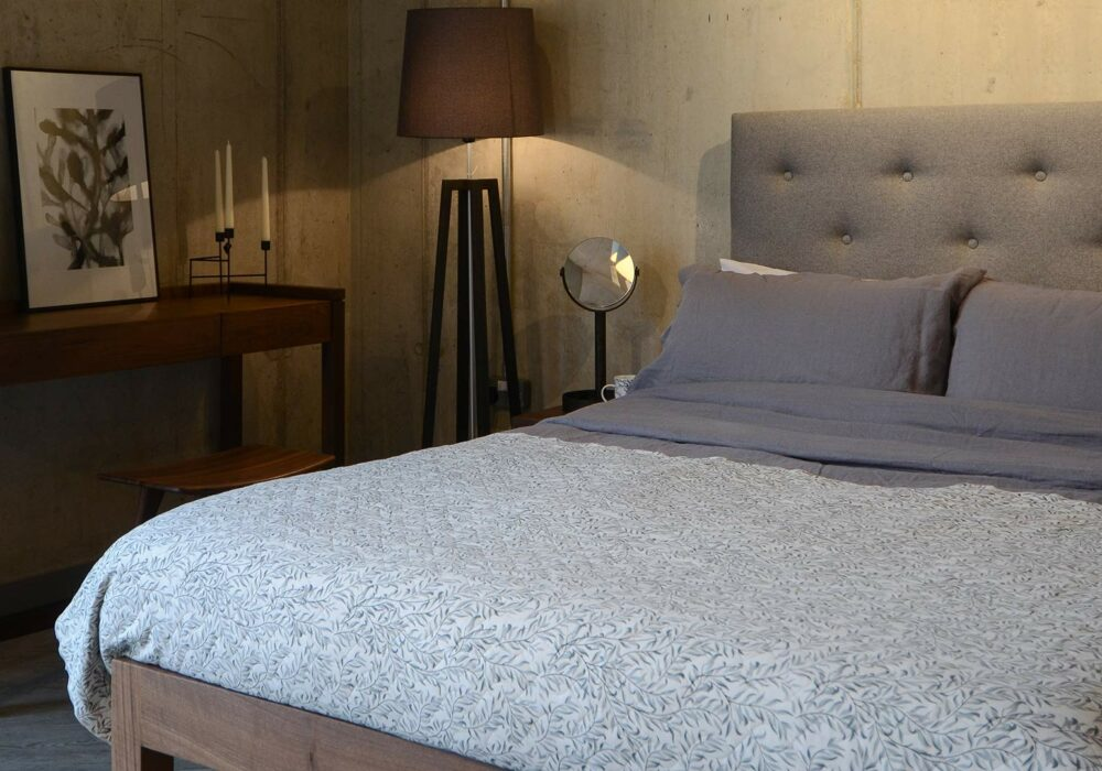 skye tall padded headboard bed with a walnut frame and grey linen bedding