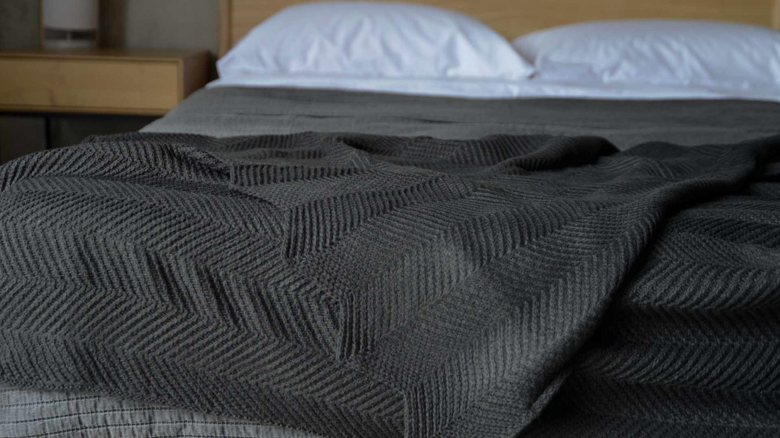 charcoal knitted throw with chevron pattern and scalloped edges
