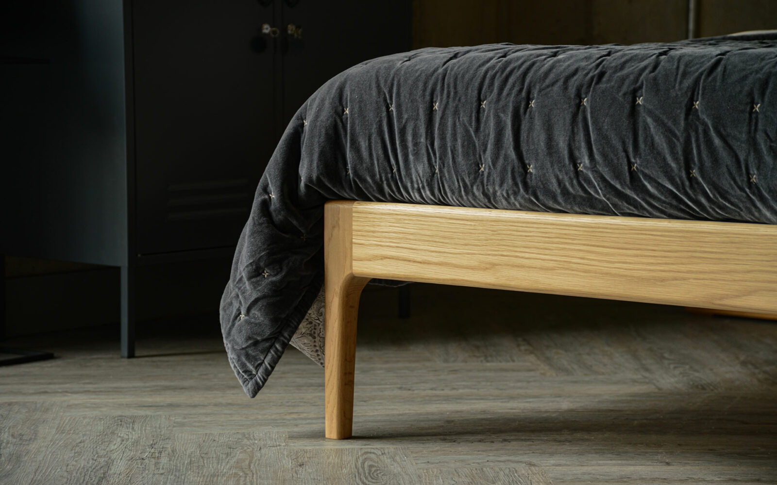 Curved oak bed leg detail with grey slate quilt