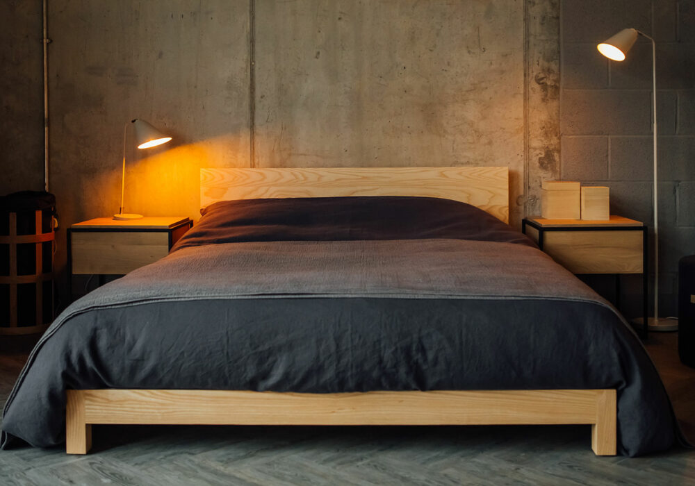 low solid wood Sonora bed base in ash with slate linen-bedding for an industrial look bedroom