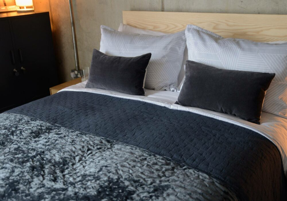 hotel style bedding featuring our crushed velvet bedspread in inky blue/grey