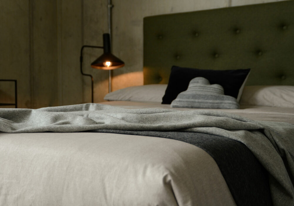 soft recycled wool fringed throws in pale grey and charcoal