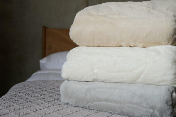 faux fur bedspreads in a choice of 3 colours shown in a stack
