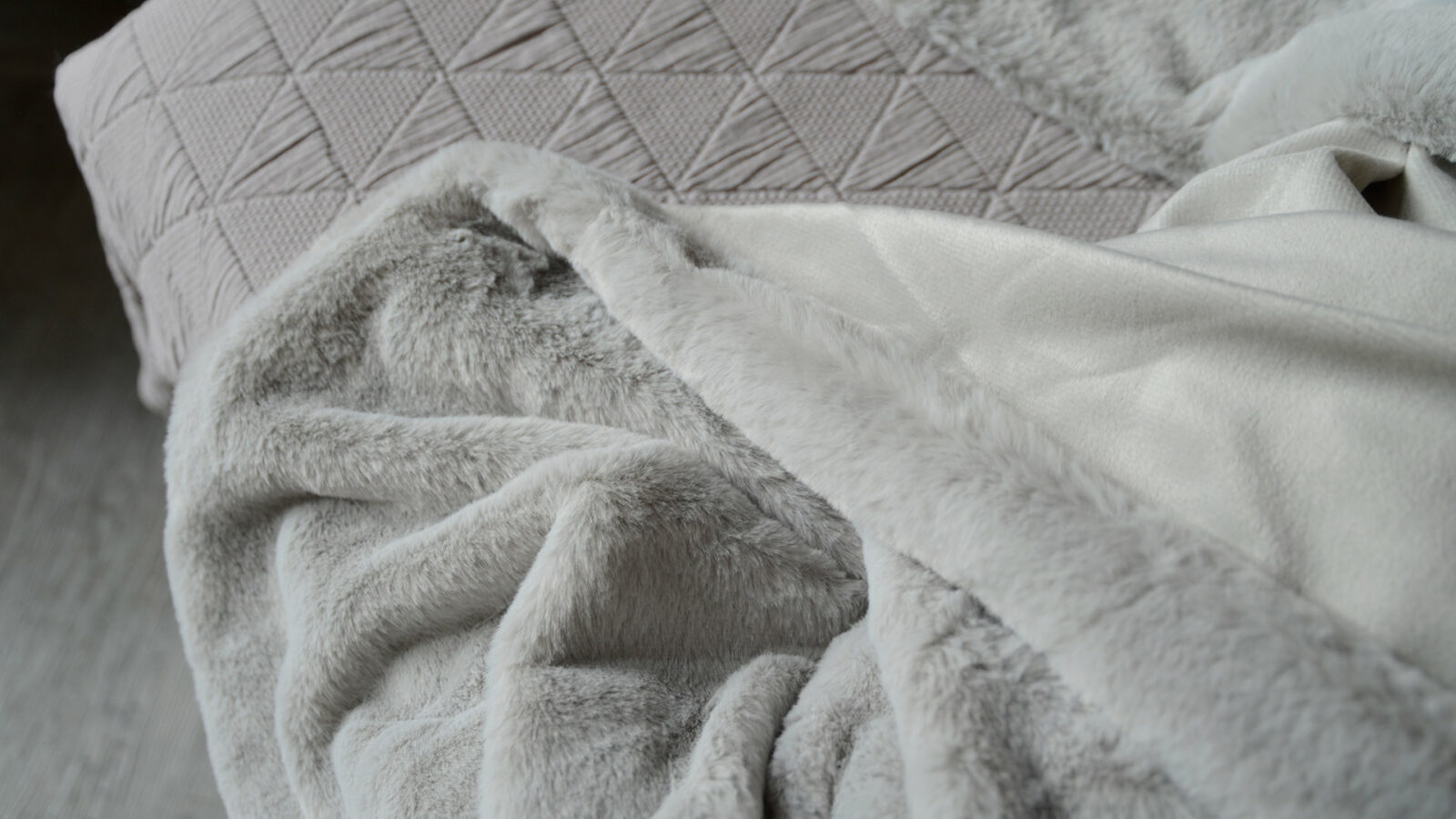 a close-up view of the soft pale grey faux fur blanket