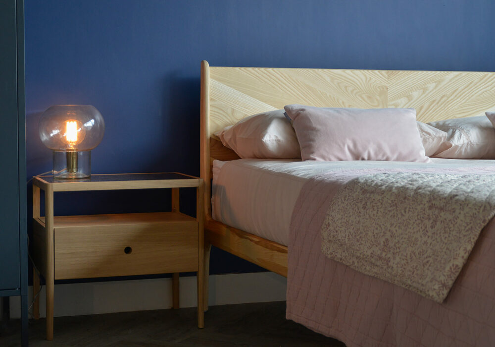 Oak wood Spindle bedside table with a storage drawer and open shelf shown with our wooden Hoxton Bed.
