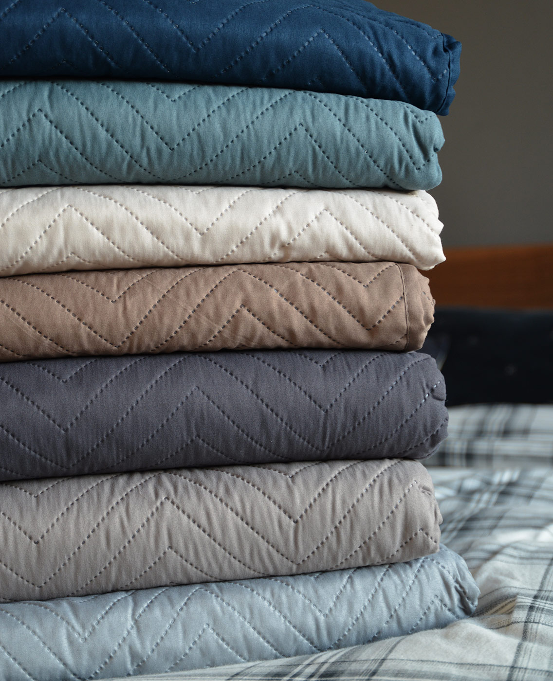 Chevron pattern lightly quilted bedspreads stacked and in a range of colours