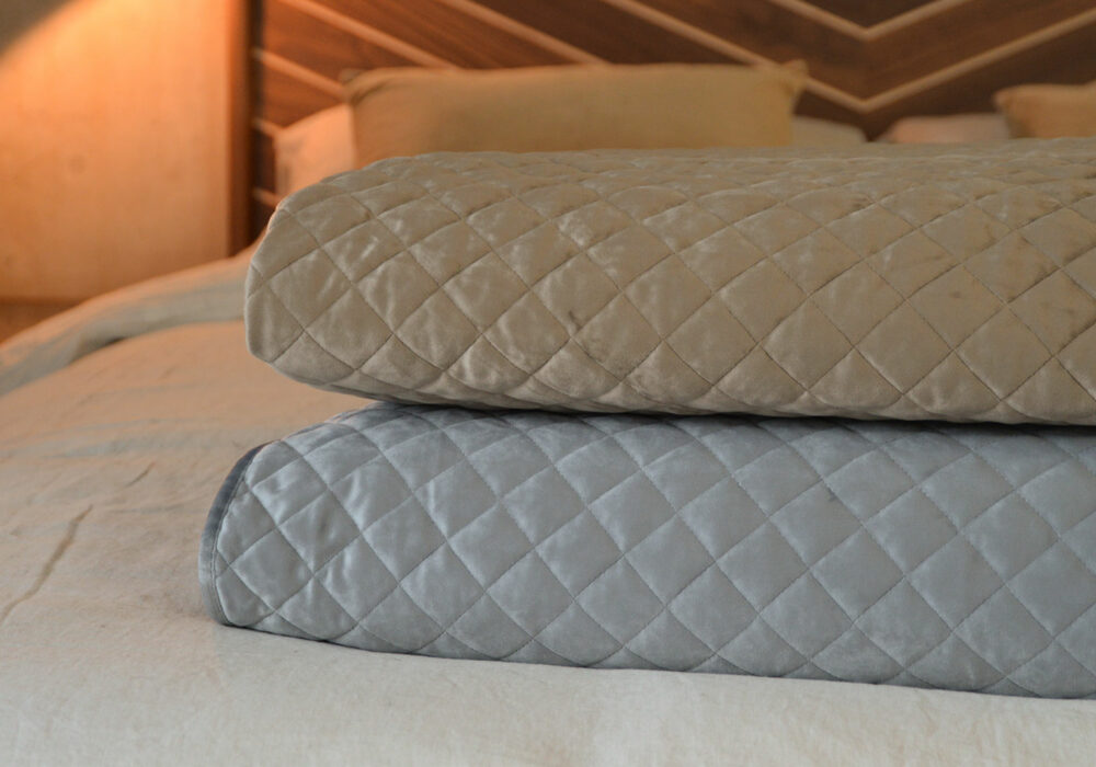 Taupe and silver grey coloured velvet-look quilted and reversible bedspreads shown together
