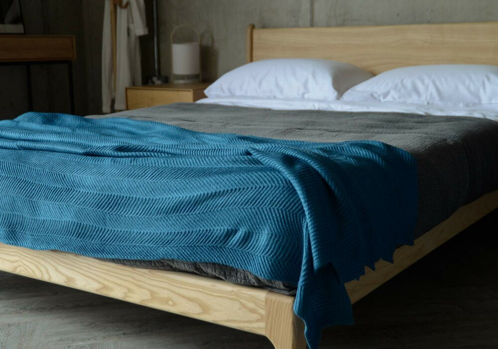 deep teal knitted throw with chevron pattern