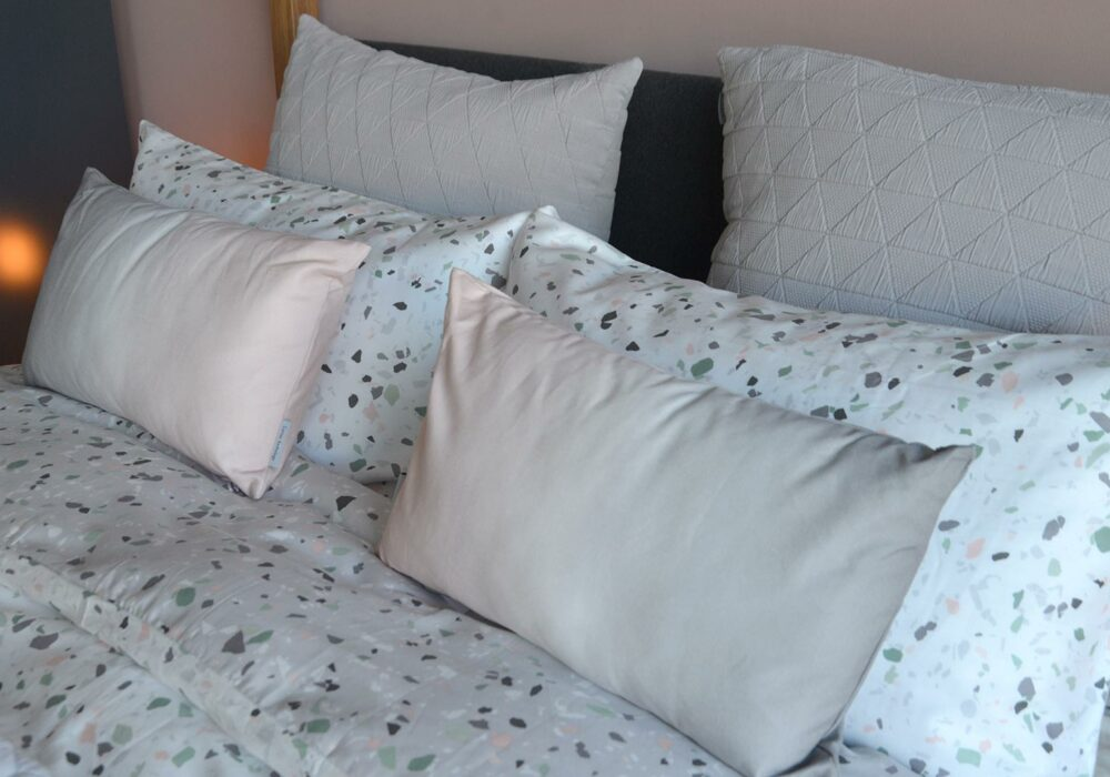 reversible terrazzo print bedding with pink ombre cushions