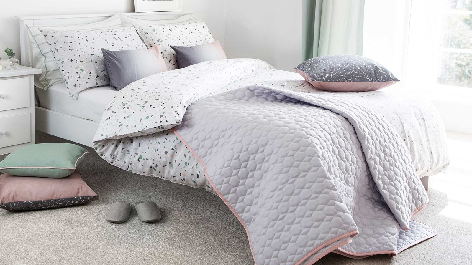 reversible terrazzo pattern duvet cover set shown with grey quilt