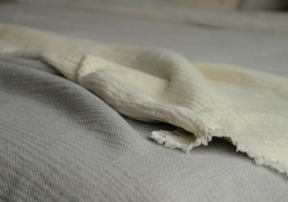 organic cotton textured bed throw in grey and ivory a close up view