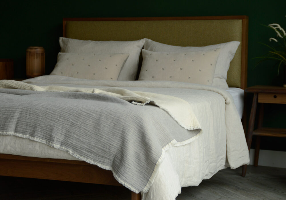 organic cotton reversible throw in pale grey and ivory shown on a kingsize bed