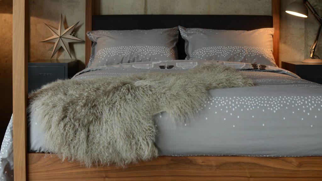 tibetan-lamb-fur-throw-pale-grey-on-log-cabin-print-bedding